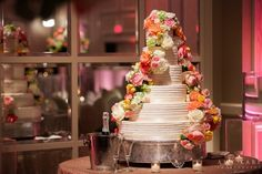 Six tiered brides white wedding cake with colorful flowers cascading down cake on silver cake stand on sequin linen with candles at October fall wedding reception at The Adolphus Hotel in Dallas, Texas - Photos by Amy Karp Photography