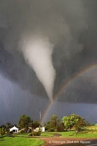 Tornado and Rainbow Over Kansas  The scene might have been considered serene if it weren't for the tornado. During 2004 in Kansas, storm chaser Eric Nguyen photographed this budding twister in a different light -- the light of a rainbow. Pictured above, a white tornado cloud descends from a dark storm cloud. The Sun, peeking through a clear patch of sky to the left, illuminates some buildings in the foreground. Sunlight reflects off raindrops to form a rainbow. By coincidence, the tornado…