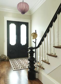 contemporary entry by Rachel Reider Interiors.  I like the black handrail and newel and the black interior door.  We have way too much white going on in our foyer.  Our front doors also have the glass inserts so we still get light through them.