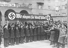 The Vienna Boys Choir, assembled under a banner that reads, We sing for Adolf Hitler! salute Adolf Hitler and his entourage during his first official visit to Vienna after the Anschluss.