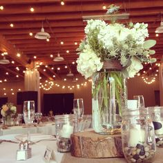 This wedding was a lot of fun. It took place in the Red Barn at Strawberry Farms in Irvine, CA. In keeping with the rustic barn theme we put our centerpieces atop some wood and the candles in mason jars with river rocks.