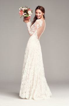 The gorgeous lace sets a vintage tone in this lovely long-sleeve wedding dress designed with a captivating illusion yoke that plunges to highlight the décolletage.