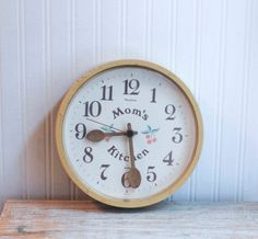 This vintage Moms Kitchen wall clock is kitsch and cute. Made by New Haven in the USA it is a soft buttery yellow on the outside, wooden spoon hands