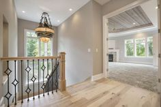 This Homeowner Loved Designing the Details of his Dream Home Including this Gorgeous Landings with a Decorative Iron Railing & Knotty Alder Floors - Creek Hill Custom Homes MN