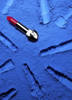 Conceptual Image 10   Has a feeling of glamour and artificial, manufactured color, bold contrast with the blue and pink. The imprints give the lipstick an interesting placement and effect.