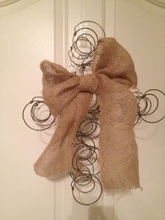From the craft room of Lenee Pearson: A cross made with bed springs and a burlap bow.