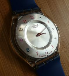 This is a 2009 'Sliding Waves' model Swatch Skin Classic (ultra thin) with NEW Replacement Strap ~ The face is a warm silver and there are Arabic numerals in various colours on the outer ring. The hands are red and stand out well against the face. | eBay!