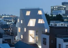 The faceted volume of this concrete housing and office block in Tokyo is punctured by a series of holes that form windows, balconies and open-air stairwells