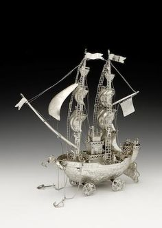 A Continental silver nef, importer's mark of John Piddington, London 1904, modelled with two masts in full sail, with sailors in the rigging and crows nests, the deck mounted with canons and sailors, and with a figure head of a male bust blowing a shell, and with two hanging anchors, the whole of four wheels, and with a large rudder,