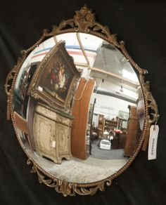 ROUND MIRROR WITH ORNATE DECORATIVE FRAME BY ATSONEA, MADE IN ENGLAND. MEASURES 22 IN. W X 23 IN. H.
