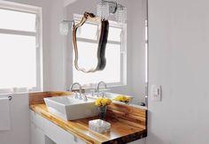 """Para ficar romântico, com ar retrô, sem deixar de ser moderno, o banheiro da suíte do casal projetado pelo arquiteto Décio Navarro tem soluções simples de grande efeito. Ele colocou um espelho da largura da bancada de madeira teça (1,60 x 0,45 m), da EG Decorações, e, em cima, instalou o espelho com moldura clássica pintada de dourado, da Apice Art, e duas arandelas vintage, da Lustreco. """"É uma maneira de emoldurar o rosto da moradora. A iluminação nas laterais ajuda na hora da maquiagem""""…"""