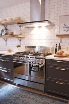brass hardware, dark cabinets, stainless steel hood and range