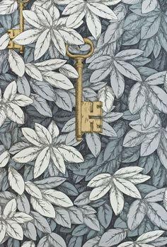 Chiavi Segrete Wallpaper Dense leaf print in grey and charcoal with hanging metallic gold keys.