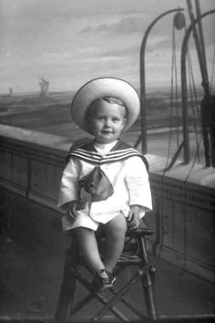 Full portrait of Master Davey sitting on a stool with the deck of ship background; wearing a sailor suit with a large collar, straw hat with upturned brim, sandals, ca 1909