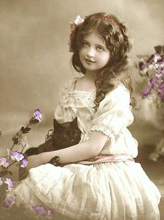 Vintage tinted photograph of lovely girl with black cat.