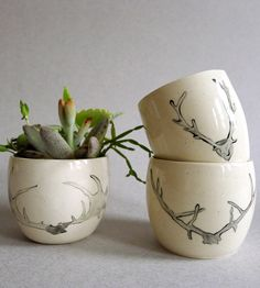 LOVE this set of ceramic planters with painted antler designs