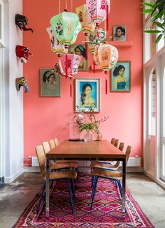 Coral walls with colorful portraits and lanterns.