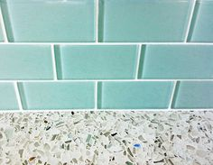 aqua glass subway tile with recycled glass counter. Notice the flecks of aqua glass in the countertop, and how the white grouting sets it all off.