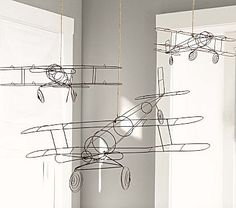 3 Wire Hanging Airplanes (one large and two small) hanging in the corner and above the drawer chests to add to the adventure.