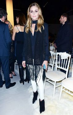 Olivia Palermo wears a fringe scarf, silk blouse, white jeans, and booties
