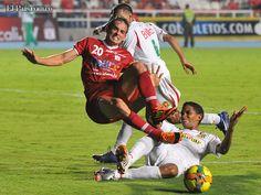 Wander Luiz refuerzo del América vuela por los aires tras la barrida de un jugador del Barranquilla.