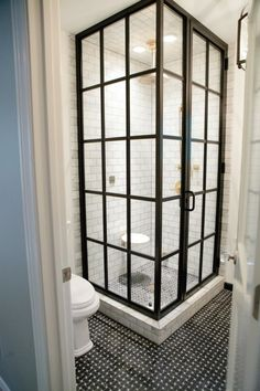 Floor to ceiling industrial window look shower with white subway tile.