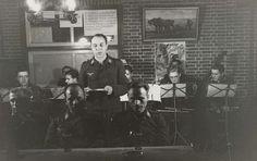 Anonymous | Orkest van de Luftwaffe, Anonymous, 1941 - 1942 | Luftwaffe militairen spelen muziek, op blaas- en snaarinstrumenten. Voor hen een standaard met muziek. Een staat te zingen. Aan de muur een plaat van een ploegende boer en een affiche: Achtung Spione.