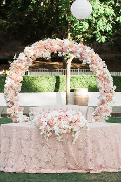 """Vo Floral Design's """"circle of love"""" does double duty as reception backdrop behind sweetheart table as well as ceremony backdrop"""