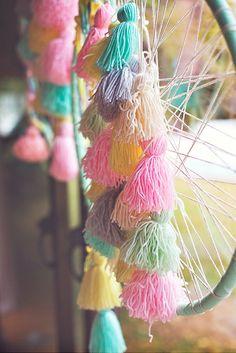 Des attrape rêve avec des pompons couleurs pastel pour décorer un anniversaire enfant