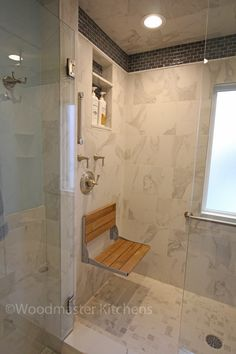 The white stone tile in this traditional bathroom design is beautifully offset by the warm wood tones of the cabinetry.  Recessed cabinetry ensures maximum use of available space in this room, including a recesssed medicine cabinet, partially recessed toilet topper cabinet, and recessed linen cabinet.  The medicine cabinet is custom framed to match the vanity.  The large shower offers luxurious bathing with rainfall and slide bar showerheads, a fold-down wooden shower seat, and built in…