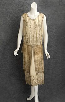"Beaded satin evening dress, c.1924. Made from ivory cream satin, the dress is lavishly embellished with faux pearls, silver beads, and silver-lined crystal beads. The enigmatic and alluring pseudo-geometric motifs showcase the dazzling Deco design. The skirt has overlay panels of matching chiffon and metallic lace. The dress slips on without closures in the ""modern style."""