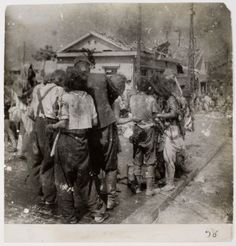 Dazed survivors huddle together in the street ten minutes after the atomic bomb was dropped on Hiroshima, August 6, 1945