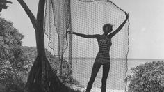 Circa 1950: A bather amuses herself with a fishing net which is hung in a pandanus tree, at Heron Island, in the Great Barrier Reef. (Three Lions/Getty Images)