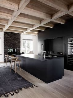 intérieur minimaliste, îlot de cuisine noir, chaises de bois, plafond en bois