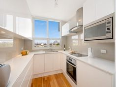 White cupboards, grey splashback, but tiled floor