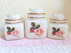 This is a beautiful set of glass jars with pink roses. There is one large jar and two smaller jars. They are not white glass but they are clear