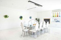 This ultra-modern space has large white tile flooring, a glass dining table, white chairs, open shelving, colorful art work and hanging light fixture.