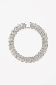 Made from silver-coloured metal in a modern twisted coil, this necklace is secured with a strong magnetic fastening.