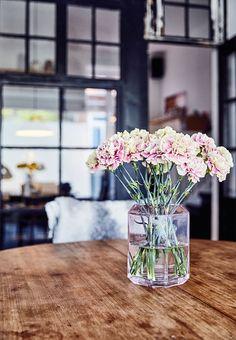En lyserød vase med blomster som feminint touch i den rå indretning