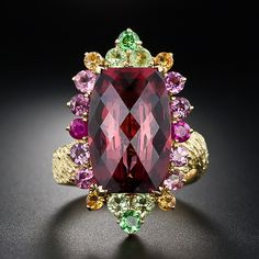 18K Garnet Estate Ring A gracefully cut 11.90 carat deep raspberry red garnet with a fully faceted top is framed in a multi-chromatic array of gemstones. The distinctively textured ring shank is reminiscent of 1960s vintage art jewelry. A one-of-a-kind jewel and conversation piece.