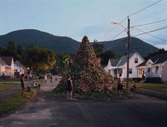 This picture is by Gregory Crewdson. His work combines different everyday places and happenings and combines them into one, creating a surreal artefact, such as this one. Or another work where someone is gardening inside. Crewdson also uses film scale lighting for his works.