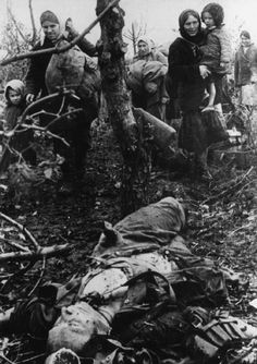 Russian women and children fleeing their destroyed village pass by the body of a German KIA. Undated. The destruction wrought on the Russian countryside by the invading Germans was enormous. The extermination of villagers was routine and the torching of dwellings and farm facilities mandatory.