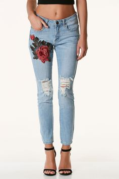 Light washed mid rise jeans with distressing in front and floral patch on one side. Five pocket design with button and zip closure.