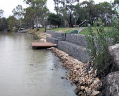 Gabion retaining wall installed by Prospect Contractors to help stabilise the river bank. Gabion Retaining Wall, Landscape Engineer, Summer Landscape, Landscape Steps, Erosion Control, River Bank, River House, Garden Structures, Outdoor Landscaping