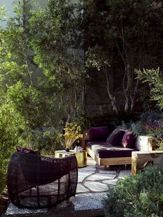 Love the purple with the deep green, the wood furniture and the large stones.