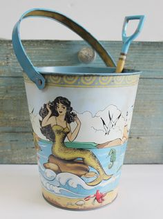 "Add a touch of elegance to your coastal kitchen or nautical garden with this food-safe Sea Beauty Sand Pail & Shovel set. Not only is it perfect for a nautical garden, but can be used as a serving piece for your beach-themed party or accent for a coastal kitchen. Pail measures 8""h x 7""w. Shovel measures 11""h x 4""w."