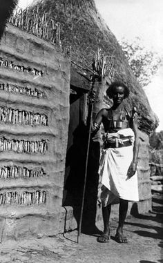 Africa | A Gala warrior stands with native dress and tools outside a gate.  Somalia.  1909 | ©Gentilucci Italo