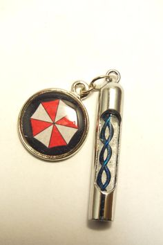 Resident Evil Mini Virus Bullet Hypo with Umbrella Charm, choose from 5 helix types. $19.00, via Etsy.