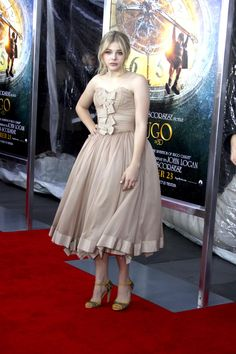 "Chloe Grace Moretz hit the red carpet in a flowing Dolce & Gabbana champagne-colored tube dress with ribbon details in the front for the ""Hugo"" premier."