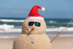 Snowman Made Out Of Sand With Santa Hat. Snowman On Beach with shells as mouth a ,